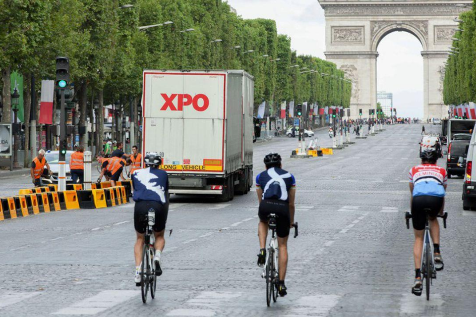Tour de France cyclists and XPO trucks