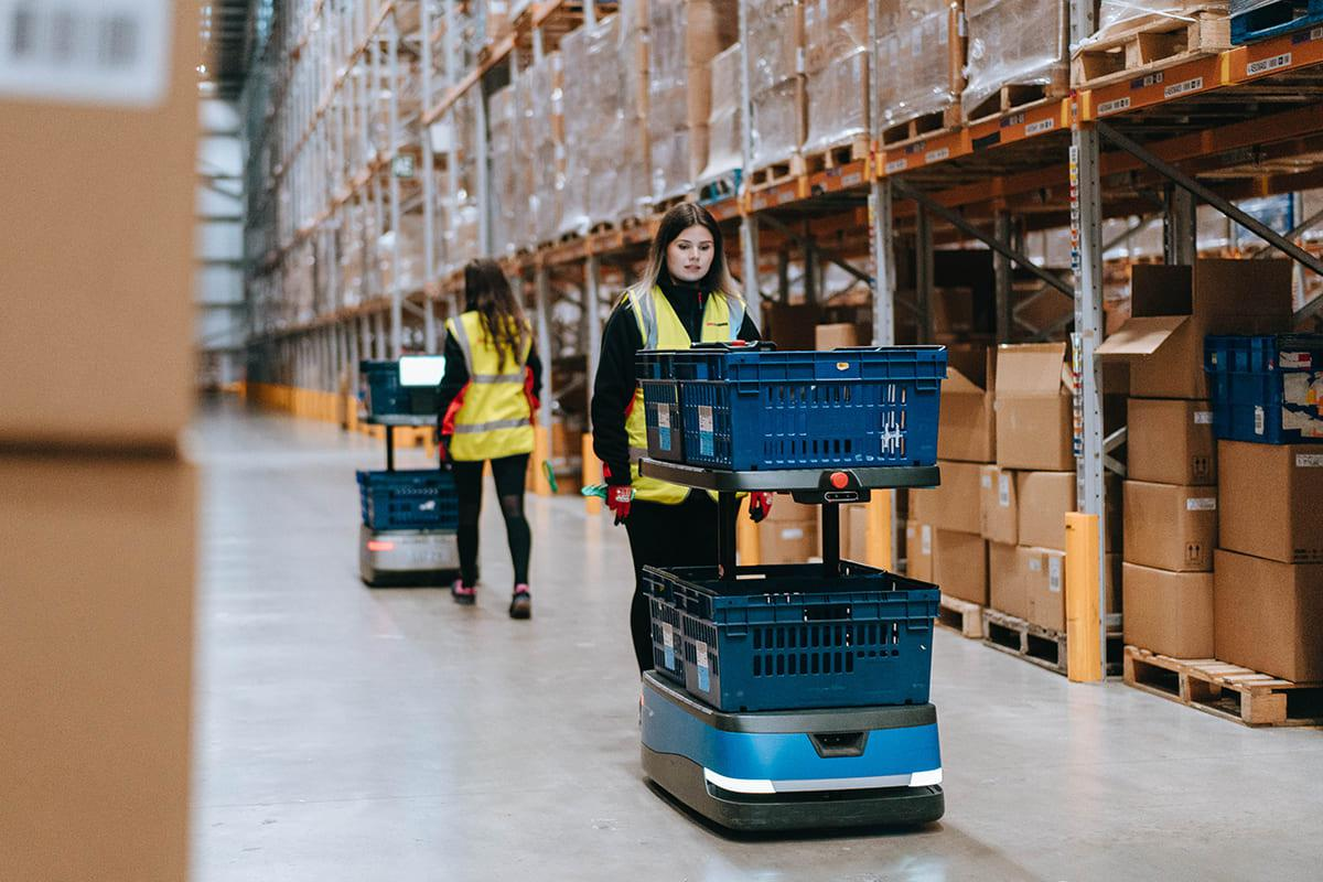 Automated cobots and employees at warehouse operation