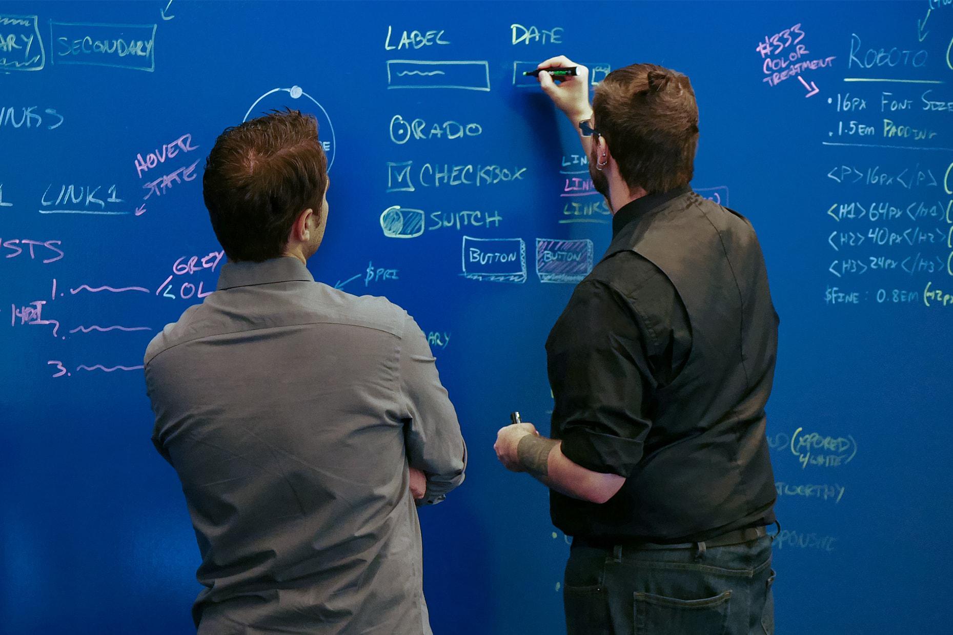 XPO UX designers working coding on a blackboard