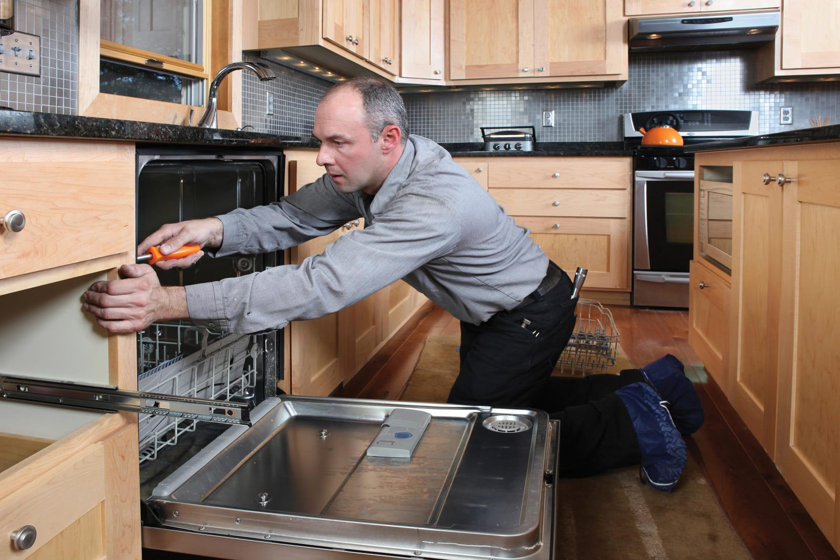 Last Mile Technician installing appliance in customers kitchen