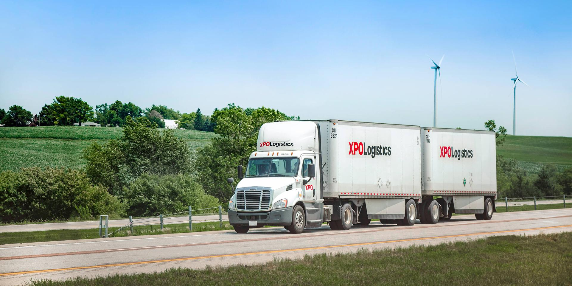 XPO LTL truck driving past wind turbines