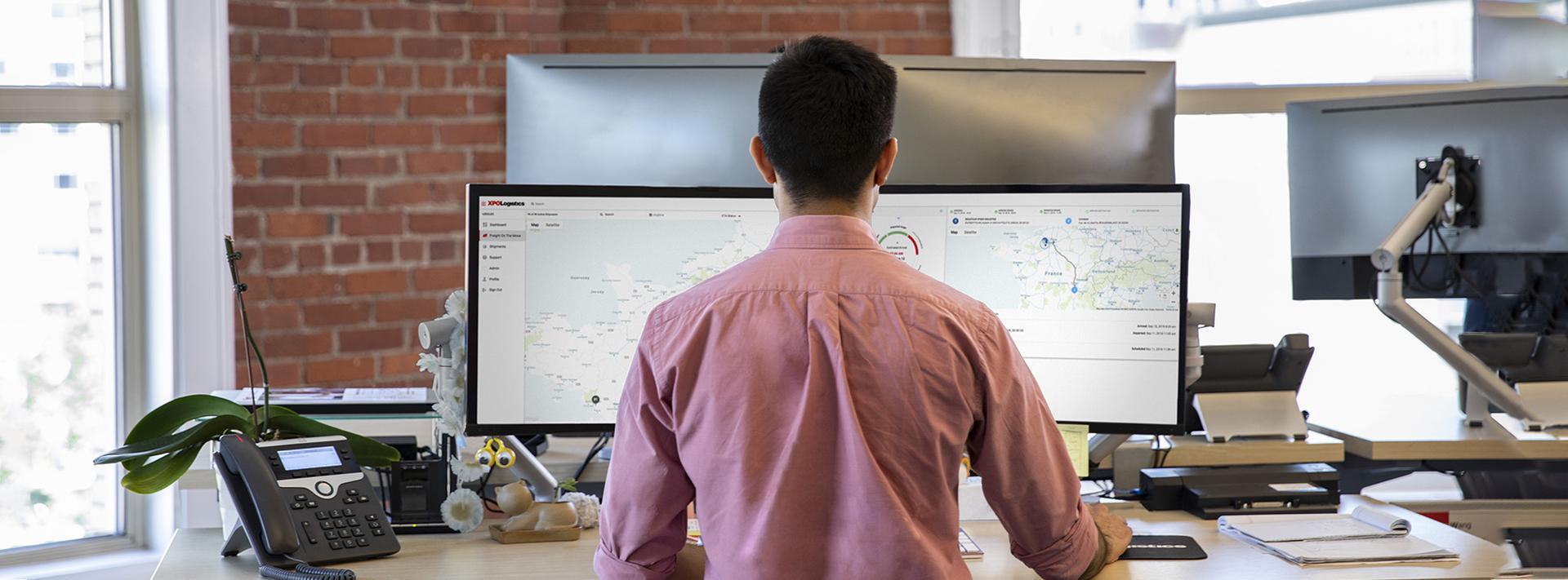 Pessoa que trabalha na plataforma XPO Connect em várias telas em um escritório moderno