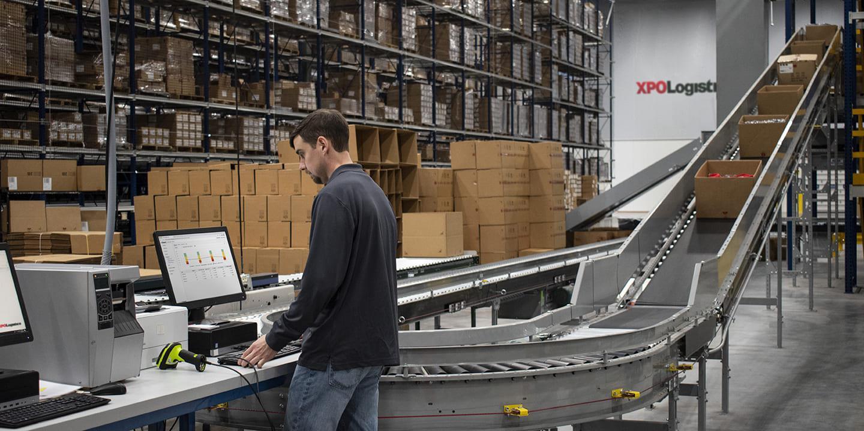Funcionário do armazém XPO gerenciando estoque na plataforma digital