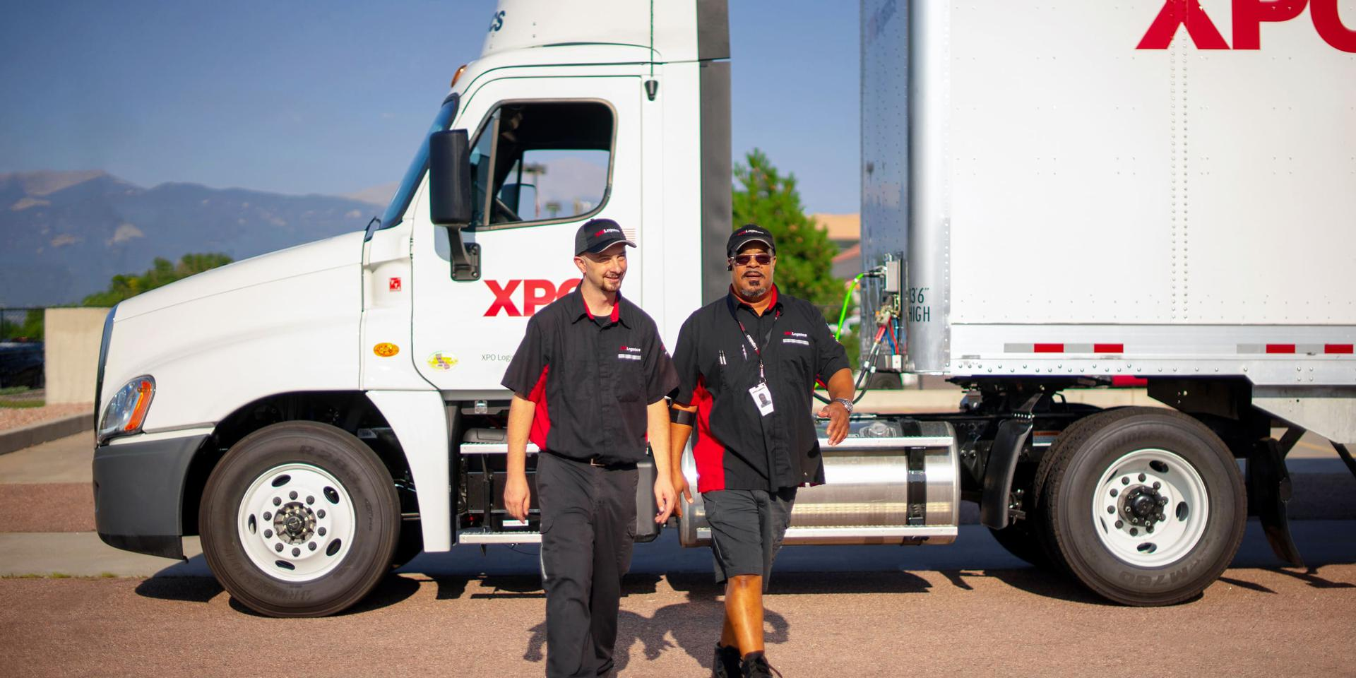 XPO Drivers walking in front of truck, on a bright sunny day with mountains in the background