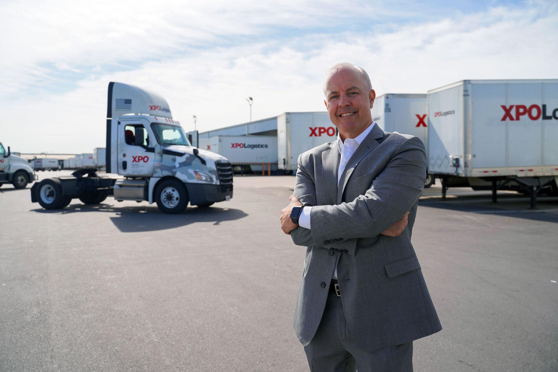Dennis McCaffrey stands in front of a military-wrapped XPO tractor.