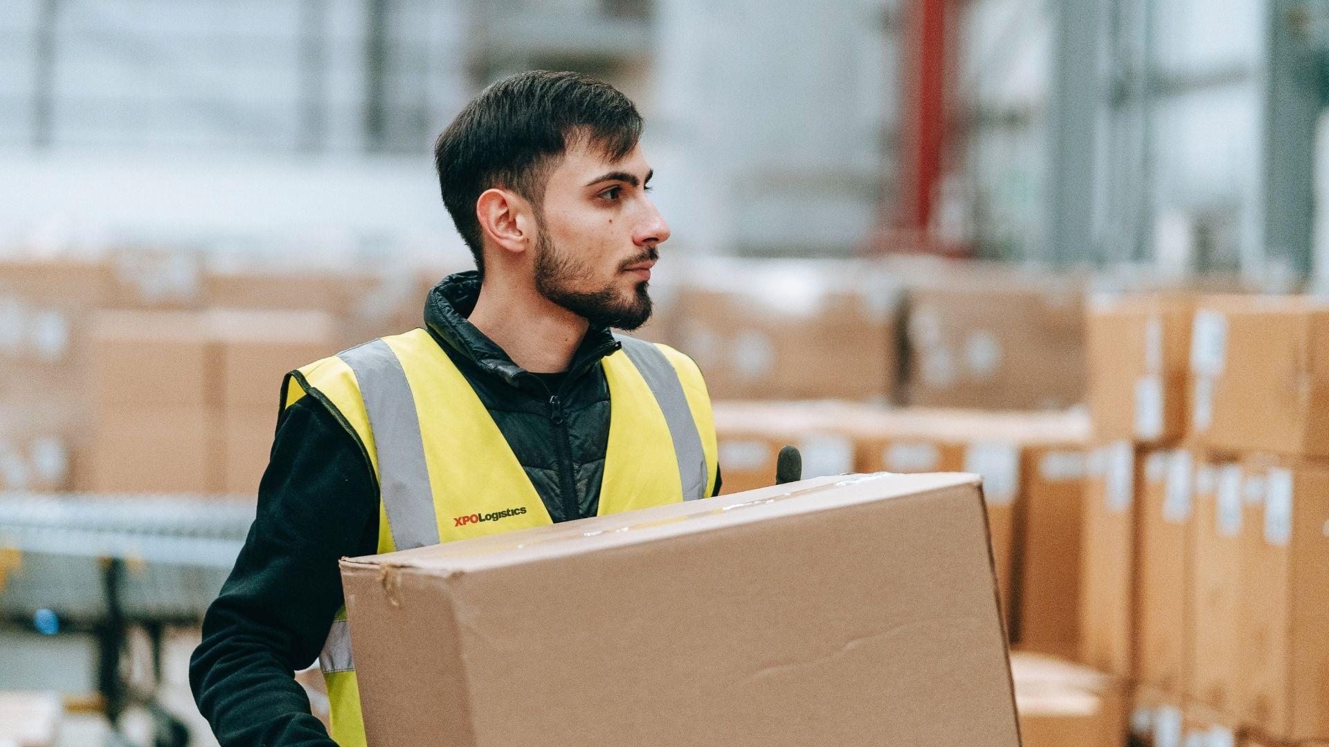 XPO employee holding a box in a warehouse