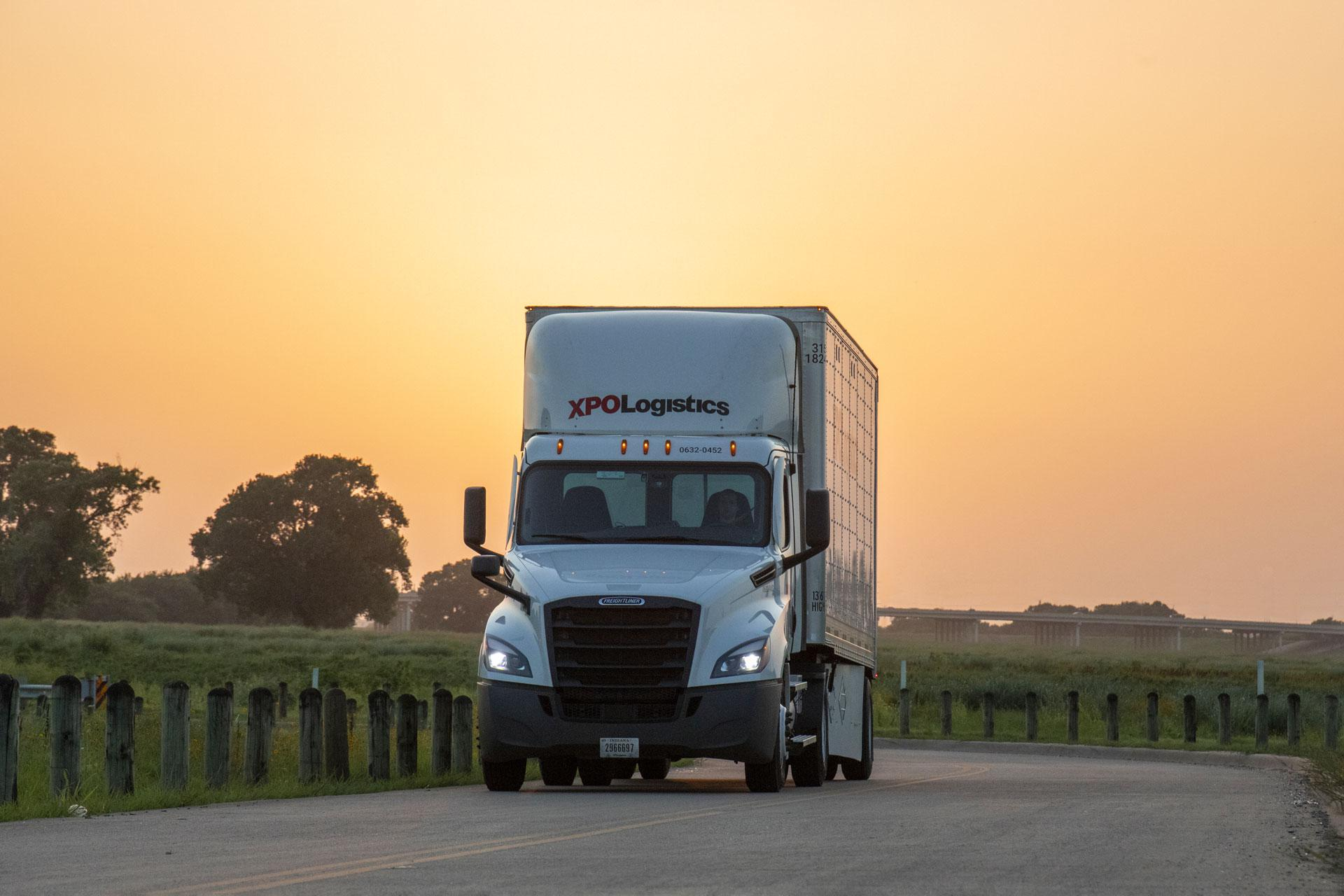 XPO truck on road during brilliant sunset
