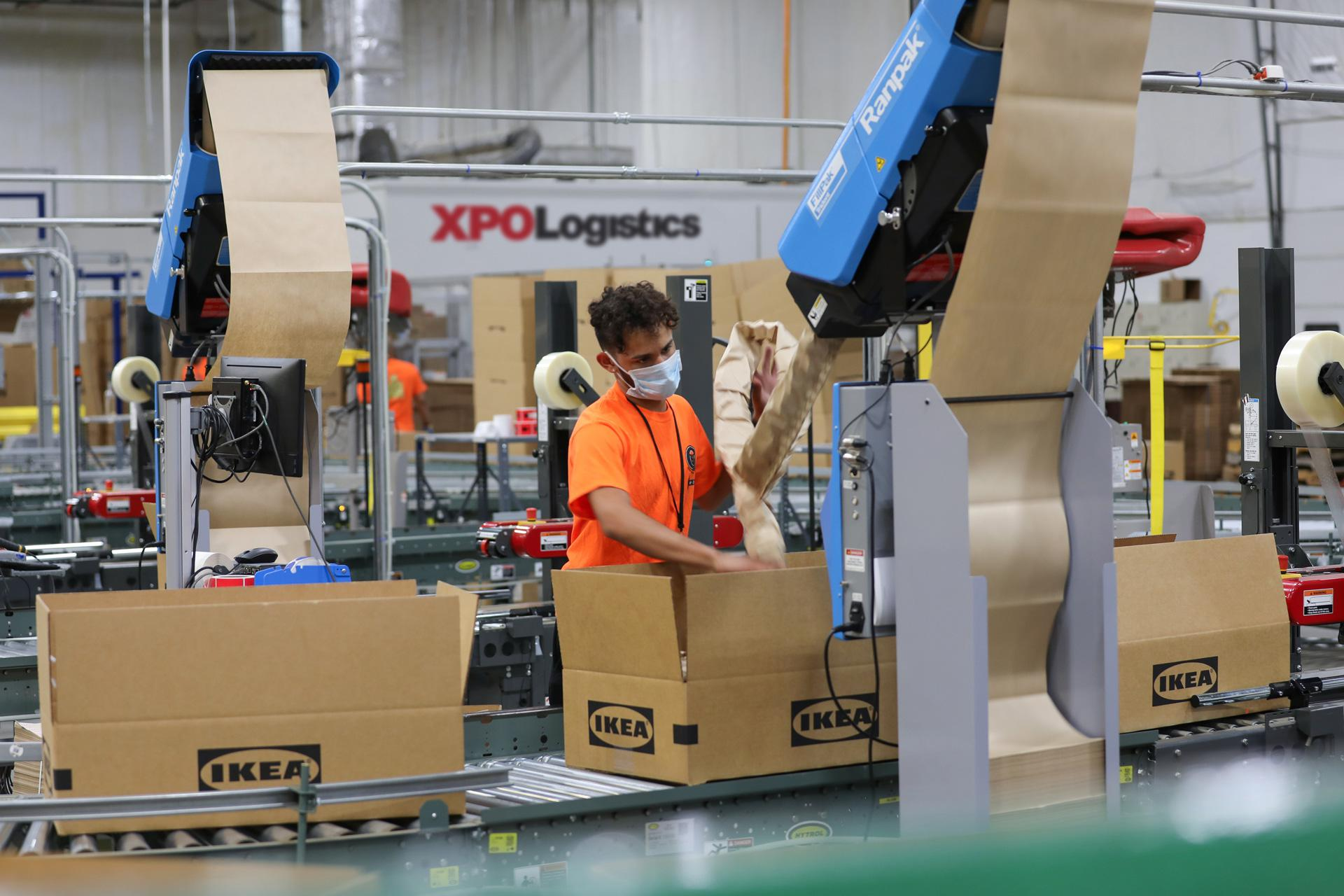 XPO employee works on IKEA packaging line.