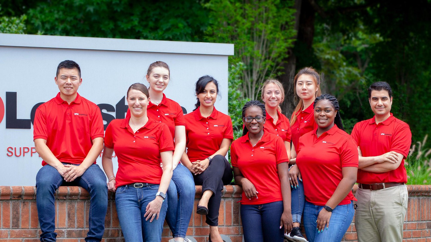 XPO supply chain interns line up in front of the company's sign in High Point, NC