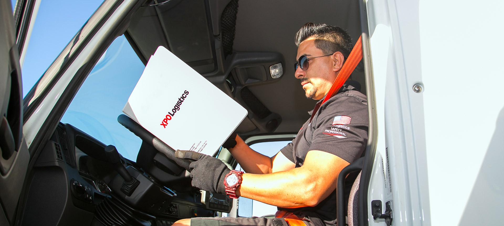 XPO driver reviews documents in truck cab