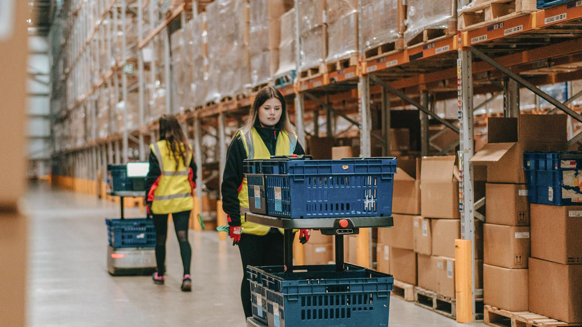 XPO Logistics employee follows behind a cobot that makes the picking process safer and easier