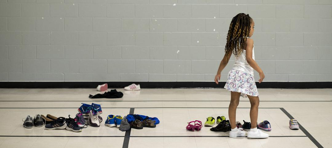 A child at school, in gym class near the sneakers