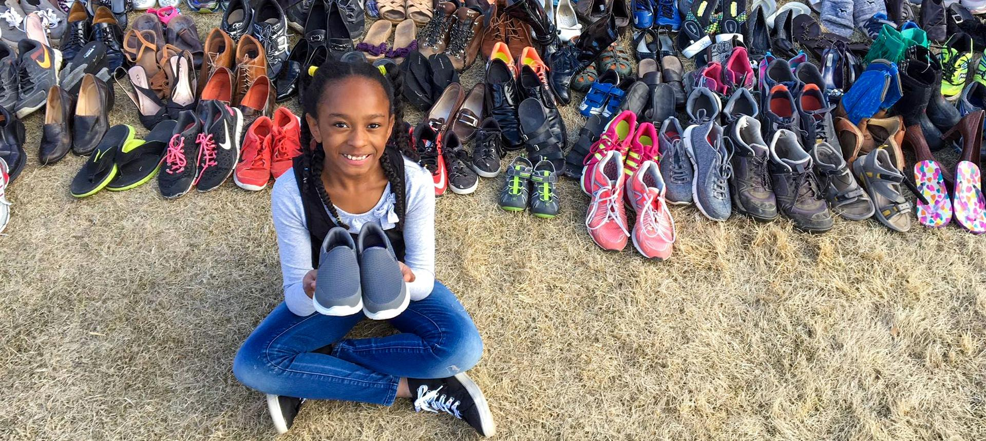 Child holds shoes donated to Soles4Souls