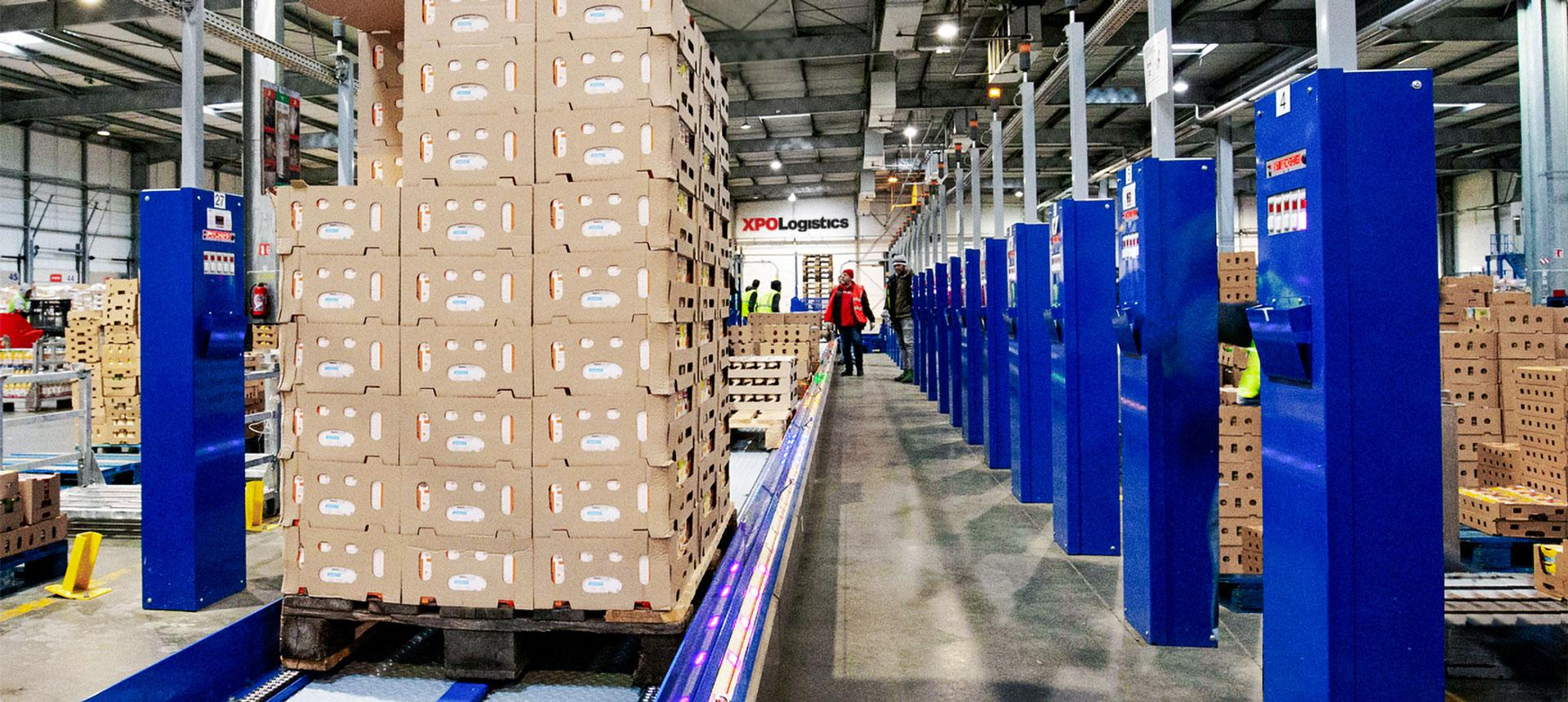 an XPO Logistics worker watches a conveyor line at a distribution center.