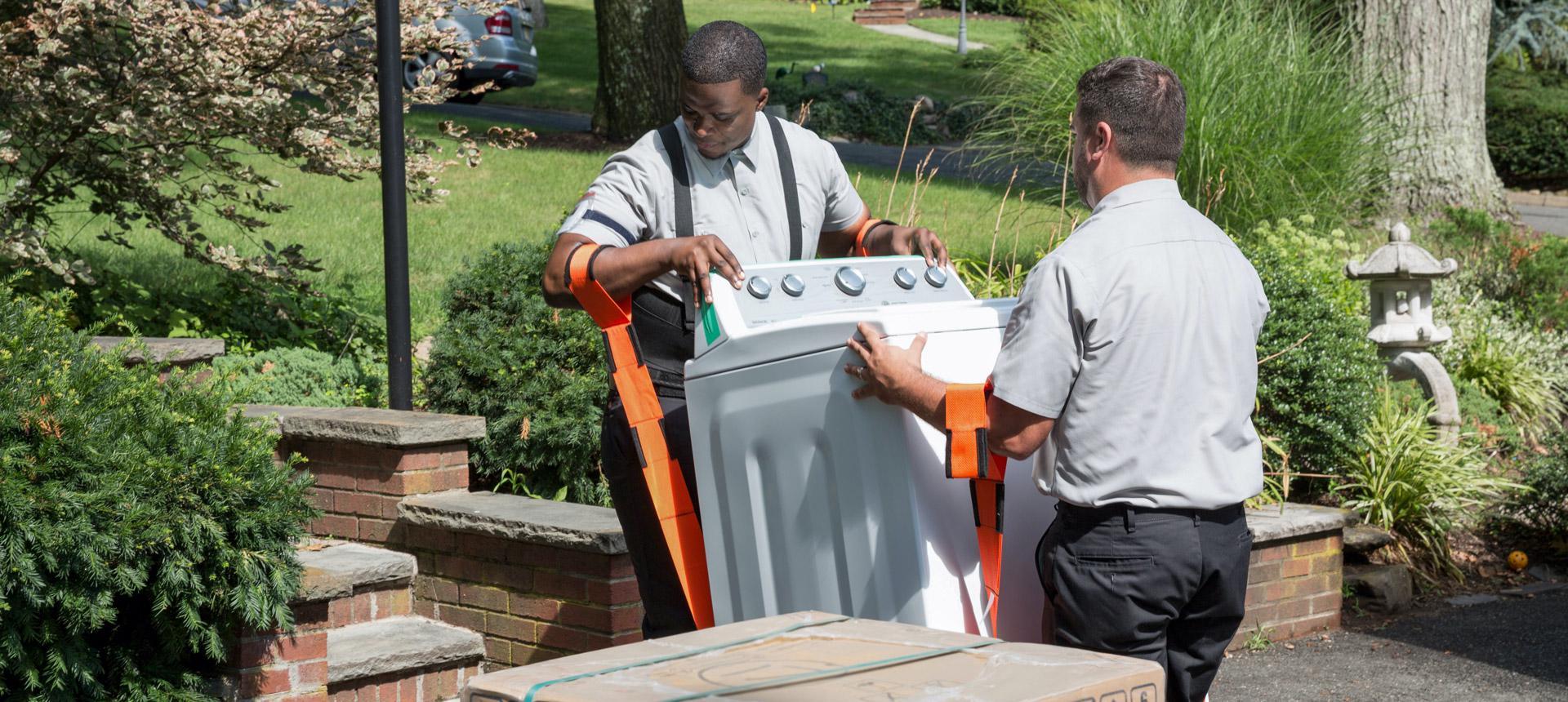 Two men handling an appliance